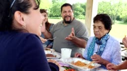 Hispanic family enjoying a meal together at a family reunion