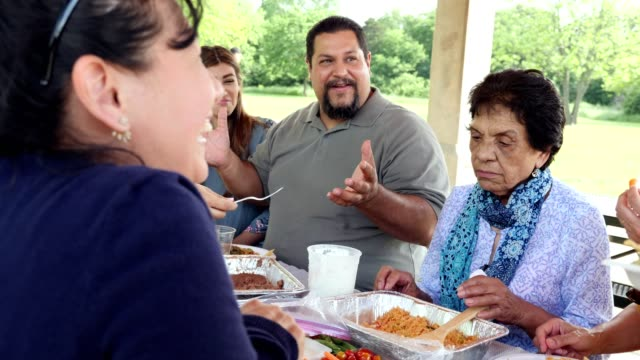 hispanic family enjoying a meal together at a family reunion - etnia latino americana video stock e b–roll