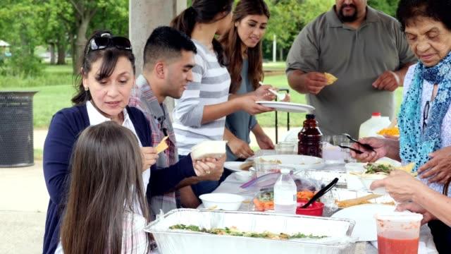 Hispanische Familie beim Mittagessen im Park
