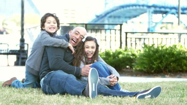 hispanic family having fun in park, boy runs up - approaching stock videos & royalty-free footage