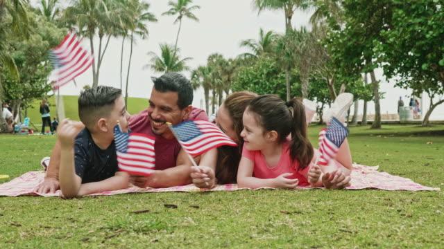vídeos de stock e filmes b-roll de hispanic family holding american flags on holiday - dia do trabalhador