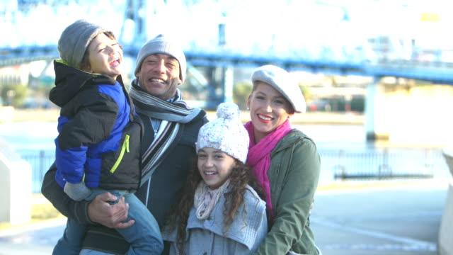 vidéos et rushes de famille hispanique sur le front de mer de ville en hiver - manteau et blouson d'hiver