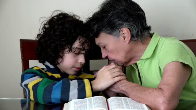 hispanic family praying or having a christian daily devotional - jesus christ stock videos & royalty-free footage
