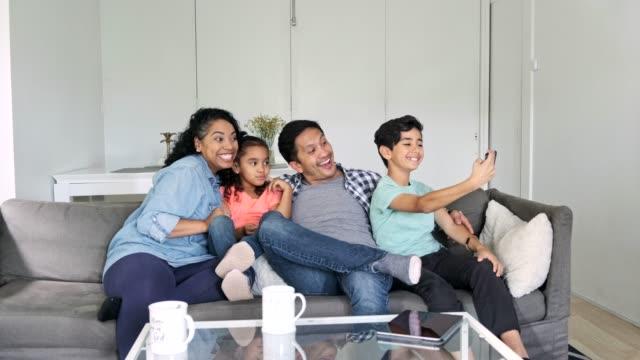 hispanic family sitting in the living room and using a smart phone - temi per la fotografia video stock e b–roll