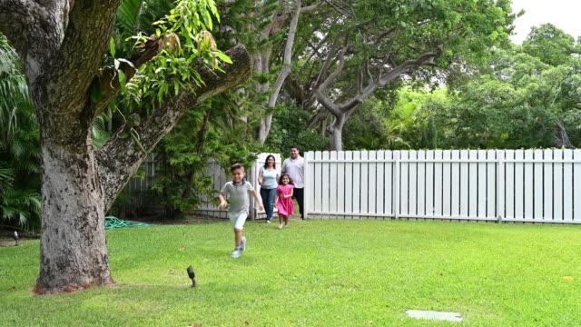 vidéos et rushes de famille hispanique marchant par la porte de jardin - clôture jardin