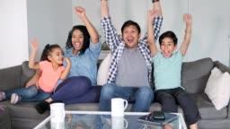 Hispanic family watching tv together and cheering in the living room