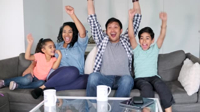hispanic family watching tv together and cheering in the living room - television show stock videos & royalty-free footage