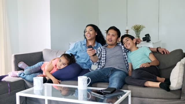 vidéos et rushes de famille hispanique regardant la télévision ensemble dans le salon - salon pièce