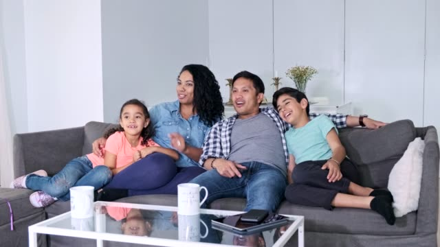 hispanic family watching tv together in the living room - latin american and hispanic ethnicity stock videos & royalty-free footage