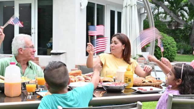 vídeos y material grabado en eventos de stock de familia hispana ondeando banderas americanas celebrando el 4 de julio - cuatro de julio