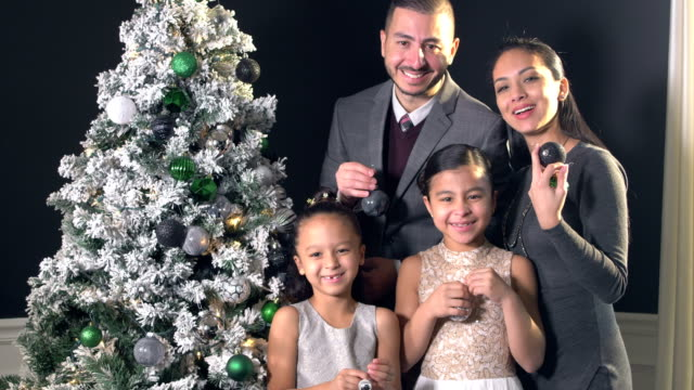hispanic family with two girls next to christmas tree - 6 7 years stock videos & royalty-free footage