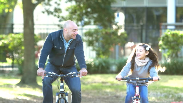 hispanic father and daughter riding bikes in park - jacket stock videos & royalty-free footage