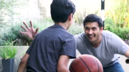 Hispanic father and son playing basketball together outdoors
