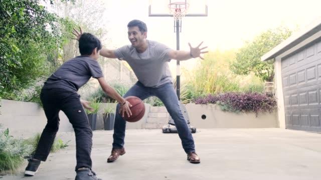 vidéos et rushes de père et fils hispaniques jouant au basket-ball ensemble à l'extérieur - trentenaire