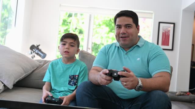 vídeos de stock, filmes e b-roll de pai e filho hispânicos jogando videogame juntos - 40 44 anos