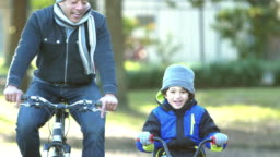 Hispanic father and son riding bikes in park