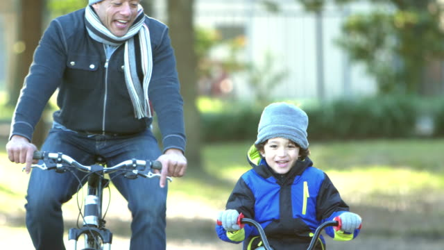 padre e figlio ispanici in bici nel parco - cappotto invernale video stock e b–roll