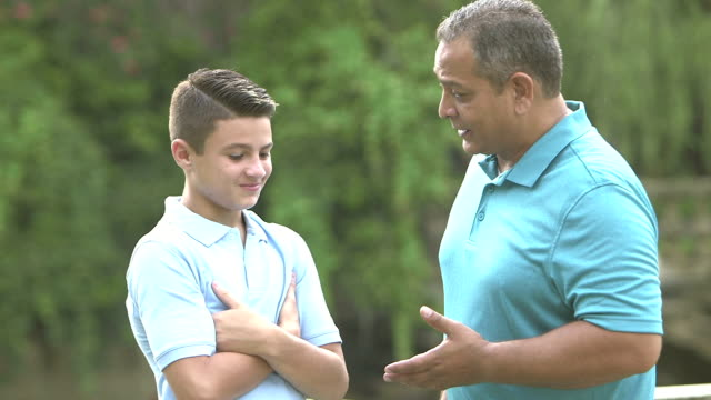 Hispanic father giving advice to teenage son