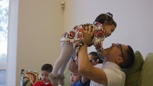hispanic father holding baby girl in the air as she kisses him - fatcamera baby stock videos and b-roll footage