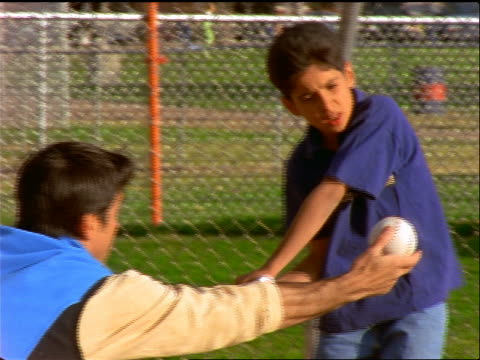 hispanic father holding baseball as son practices hitting it with bat - baseball bat stock videos & royalty-free footage