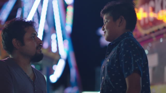 a hispanic father leans down to talk to his son on the midway of a carnival - wilmington north carolina stock-videos und b-roll-filmmaterial