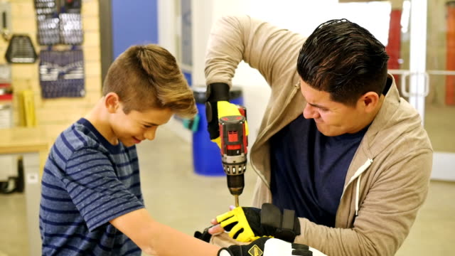 Hispanic father or instructor in woodworking workshop instructs preteen boy with project