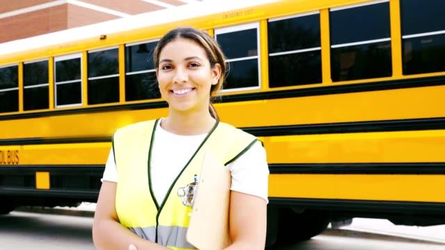 vídeos de stock, filmes e b-roll de motorista de ônibus hispânica parada na frente de ônibus escolar - só uma mulher de idade mediana