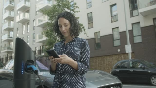vídeos y material grabado en eventos de stock de hispanic female charging electric car at charging station in city - coche eléctrico coche alternativo