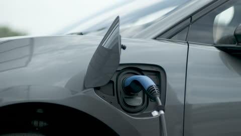 vídeos y material grabado en eventos de stock de hispanic female charging electric car at charging station on motorway - coche eléctrico coche alternativo