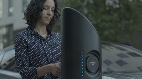vídeos y material grabado en eventos de stock de hispanic female charging electric car at charging station on the street - coche eléctrico coche alternativo