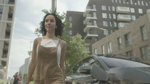 vídeos y material grabado en eventos de stock de hispanic female charging electric car on street outside home in residential area - coche eléctrico coche alternativo