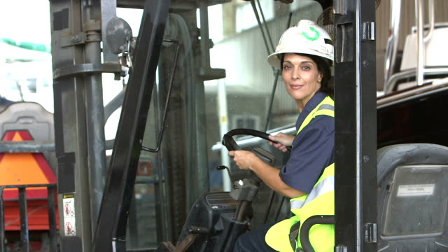 Hispanic female construction worker climbs onto forklift
