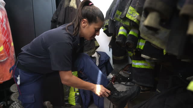 hispanic female firefighter in late 30s tying bootlaces - fire station stock videos & royalty-free footage