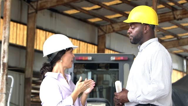 Hispanic female manager wearing hardhat, talking to man