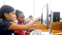 A Hispanic female middle school student tutors an African American female elementary student on a computer at STEM school