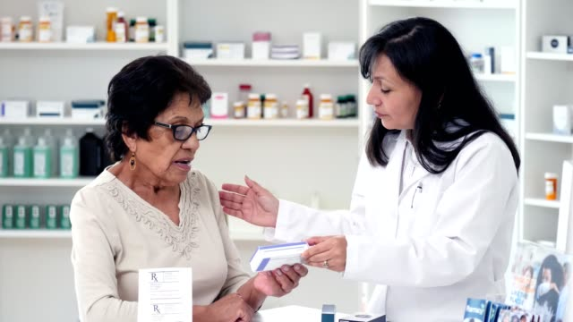 hispanic female pharmacist explains medication to senior woman - mid adult women stock videos & royalty-free footage