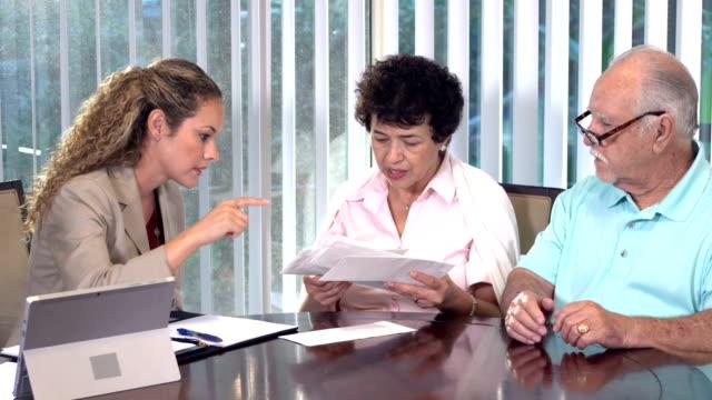 vídeos y material grabado en eventos de stock de asesor financiero hispano ayudando a parejas mayores - pareja heterosexual