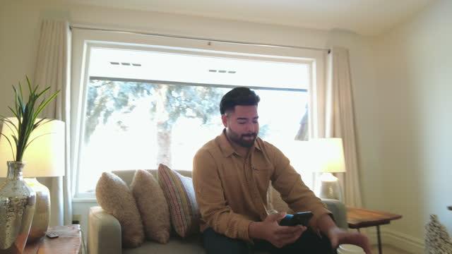 vídeos de stock, filmes e b-roll de geração hispânica z jovem adulto homem trabalhando em casa usando tecnologia 4k vídeo - parte de uma série
