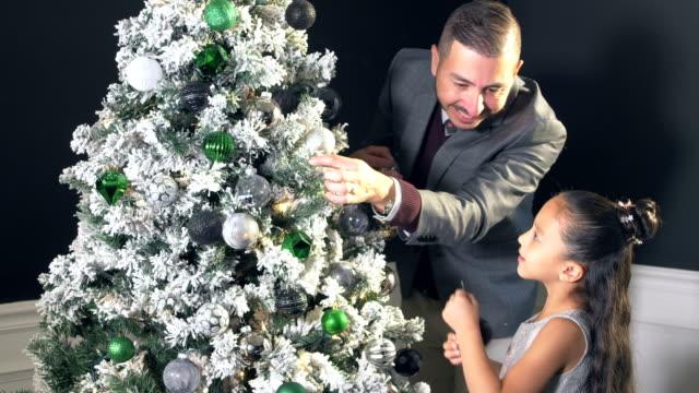 vidéos et rushes de fille et père hispanique décorant l'arbre de noël - cravate