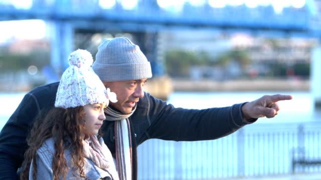 vídeos y material grabado en eventos de stock de niña y padre hispanos en el paseo marítimo de la ciudad, en invierno - abrigo de invierno