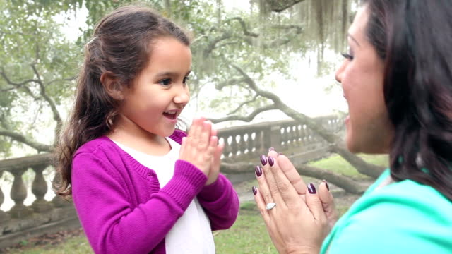 Hispanic girl and mother in park playing patty cake