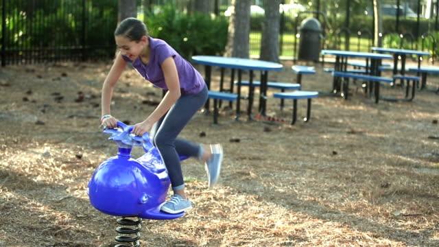 vídeos y material grabado en eventos de stock de chica hispana en el patio de recreo en el paseo de primavera - balancearse