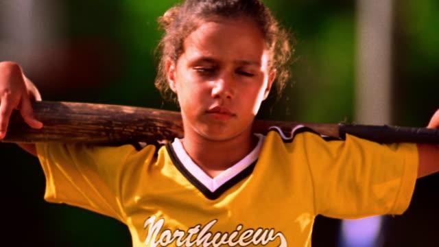 ms pan portrait hispanic girl in baseball uniform with baseball bat on shoulders / florida - baseball uniform stock videos & royalty-free footage