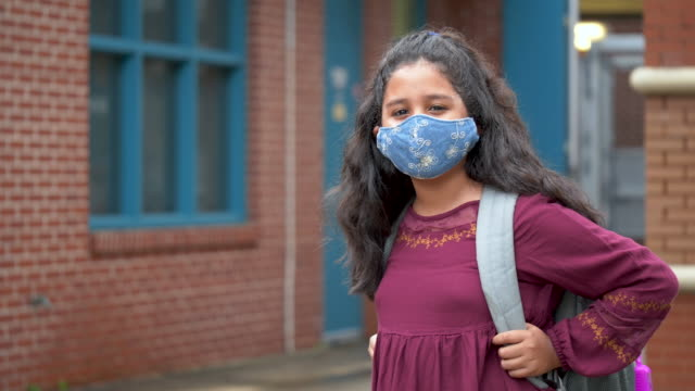 hispanic girl outside elementary school with face mask - elementary school building stock videos & royalty-free footage