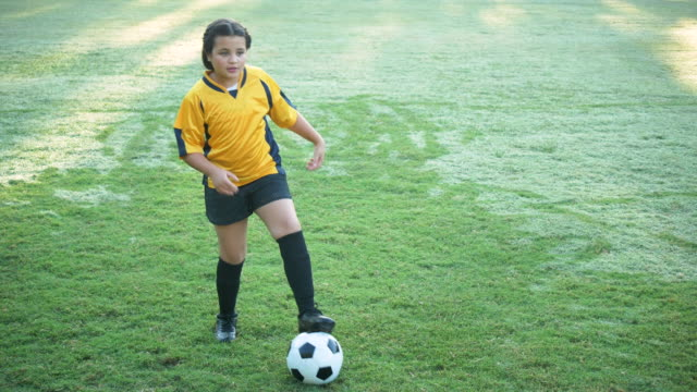 hispanic girl playing soccer, passing the ball - soccer uniform stock videos & royalty-free footage
