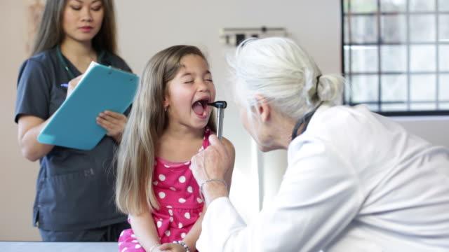 Hispanic Girl's Pediatrician Visit, Throat