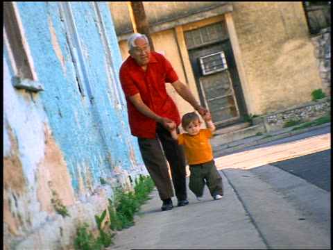 CANTED Hispanic grandfather walking with toddler outdoors by houses with peeling paint