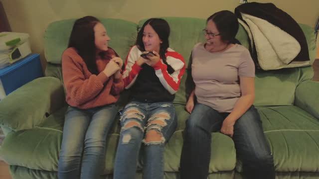 stockvideo's en b-roll-footage met spaanse grootmoeder en kleindochters hebben leuke quality time op sofa 4k videoserie - generation z
