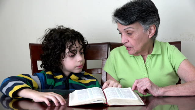 hispanic grandmother and grandson studying the bible - bible stock videos & royalty-free footage