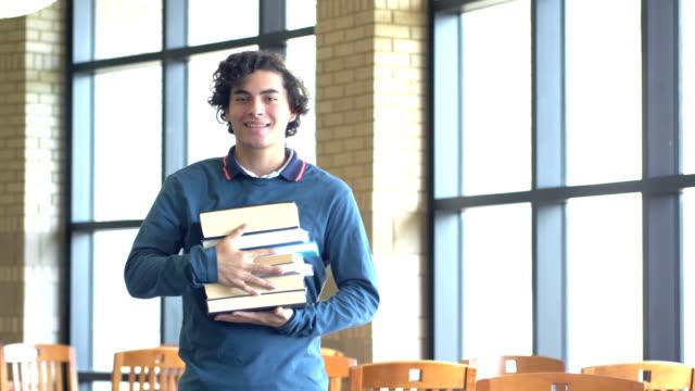 vídeos de stock, filmes e b-roll de estudante latino-americano da high school com a pilha de livros didáticos - só um menino adolescente